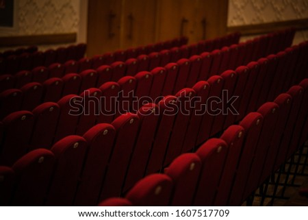 empty red seats in the auditorium in the half-darkness at a live performance. wine chairs #1607517709