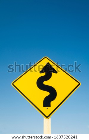 Yellow road sign with black curving arrow warning of dangerous curves against blue sky #1607520241