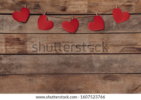 Old wooden background with a garland of red hearts. Natural rope and clothespins. Concept of recognition of love, romantic relationships, Valentine's day in grunge style. Copy space #1607523766