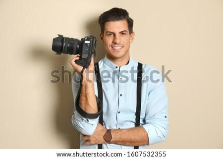 Professional photographer working on beige background in studio