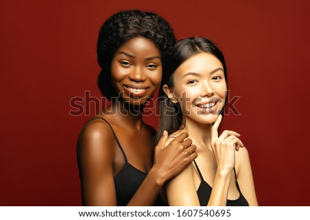 Multi Ethnic Group of beauty Womans with diffrent types of skin  together and looking on camera. Two Diverse ethnicity women -  African and Asian posing and smiling against red background. #1607540695