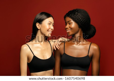 Multi Ethnic Group of beauty Womans with diffrent types of skin  together and looking on camera. Two Diverse ethnicity women -  African and Asian posing and smiling against red background. #1607540698