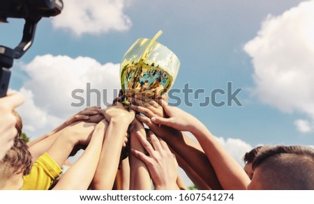 Kids in sports team lift up the golden cup trophy after winning the final tournament match. Children celebrate success in sports. Winning championship in sports Royalty-Free Stock Photo #1607541274