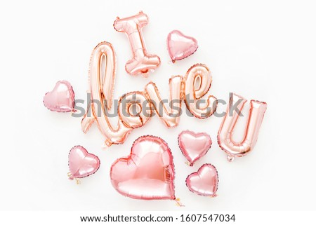 """Pale pink Foil Balloons in the shape of the word """"I Love You"""" with hearts on white background. Love concept. Holiday, celebration. Valentine's Day or wedding/bachelorette party decoration."""
