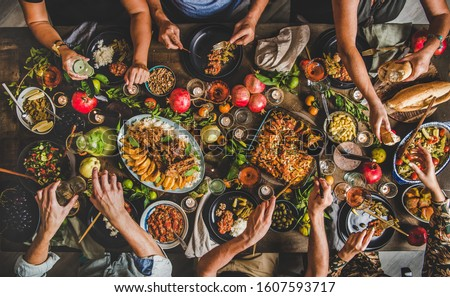 Turkish cuisine family feast. Flat-lay of people celebrating with lamb chops, quince, bean, salad, babaganush, rice pilav, pumpkin dessert, lemonade over rustic table, top view. Middle East cuisine #1607593717