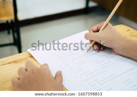 English exams test student in school, university students holding pencil for testing exam writing answer sheet or exercise for taking in assessment paper on table classroom. Education study Concept #1607598853