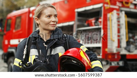 Portrait of young woman firefighter standing near fire truck.  Royalty-Free Stock Photo #1607599387