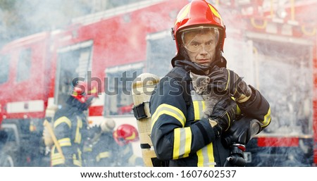 Firefighter in fire fighting operation. Portrait of heroic fireman in protective suit and red helmet holds saved cat in his arms, second fireman is out of focus near fire engine #1607602537