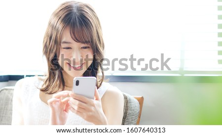 Young asian woman using a smart phone. Royalty-Free Stock Photo #1607640313