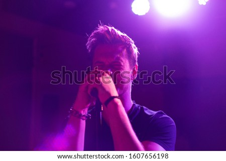 Young handsome guy emotionally sings and speaks into the microphone #1607656198