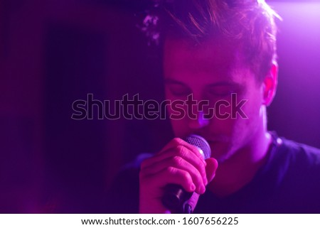 Young handsome guy emotionally sings and speaks into the microphone #1607656225