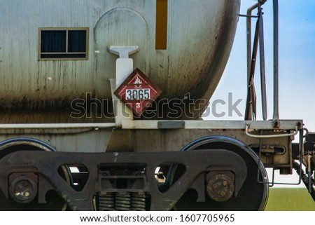 Close up of the tank car of a canadian freight train with 3065 warning sign, category 3. Signs indicate transportation of toxic and flammable liquid