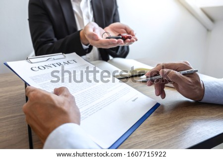 Car rental and Insurance concept, Young salesman giving car's key to customer after sign agreement contract with approved for rent or purchase. #1607715922
