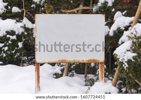 Empty billboard for advertising poster at street covered in Snow on winter day.