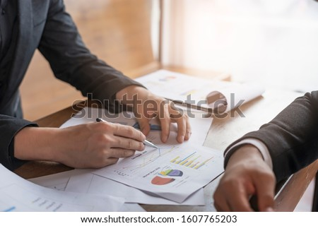 businessmen having a meeting discussing work and showing statistics and planning of the business, by pointing a pen at the graph a piece of paper, sitting across from each together on a wooden chair #1607765203