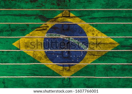 National flag  of Brazil on a wooden wall background. The concept of national pride and a symbol of the country. Flags painted on a wooden fence with a rope #1607766001
