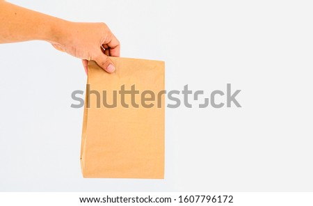 hand holding paper bag on white background #1607796172