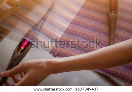 Woman working on weaving machine for weave handmade fabric. Textile weaving. Weaving using traditional hand weaving loom on cotton strands. Textile or cloth production in Thailand. Asian culture. #1607849437
