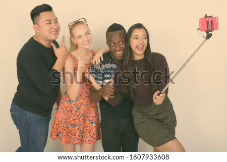 Studio shot of happy diverse group of multi ethnic friends smiling while taking selfie picture with mobile phone on selfie stick together