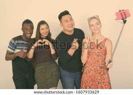 Happy diverse group of multi ethnic friends smiling and posing while taking selfie picture with mobile phone on selfie stick together