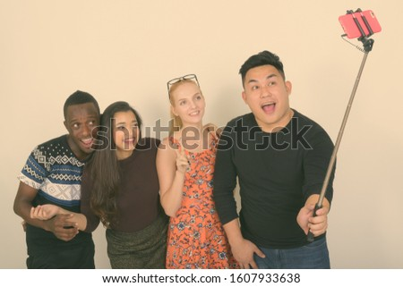 Happy diverse group of multi ethnic friends smiling while giving peace sign and taking selfie picture with mobile phone on selfie stick together
