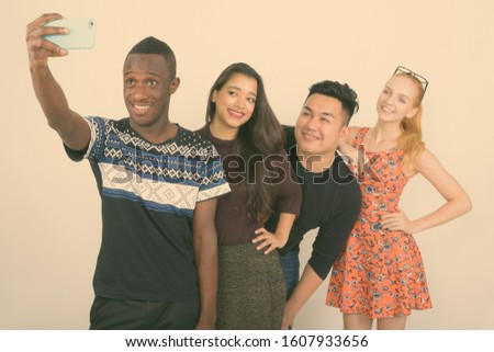 Studio shot of happy diverse group of multi ethnic friends smiling and leaning on shoulder while taking selfie picture with mobile phone together
