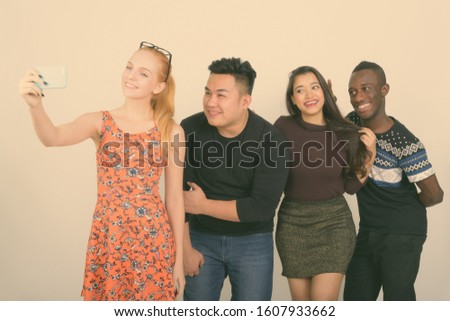 Happy diverse group of multi ethnic friends smiling while taking selfie picture with mobile phone together