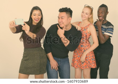 Studio shot of happy diverse group of multi ethnic friends smiling and posing while taking selfie picture with mobile phone together