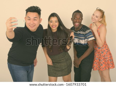 Studio shot of happy diverse group of multi ethnic friends smiling while taking selfie picture with mobile phone together