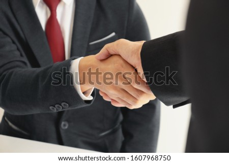 executive hand shaking at a office #1607968750