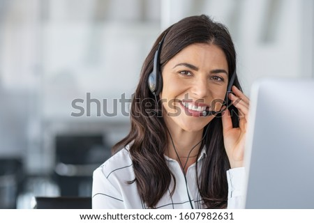 Call center agent with headset working on support hotline in modern office with copy space. Portrait of mature positive agent in conversation with customer over headset looking at camera. #1607982631