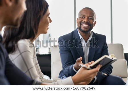 Successful businesspeople having a meeting in office and sitting on couch. Multiethnic business team working on new project and smiling. Businessman explaining documents to mature woman in office. Royalty-Free Stock Photo #1607982649