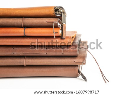 A stack of leather-bound journals, notebooks, cases and wallets set on a plain white background. #1607998717