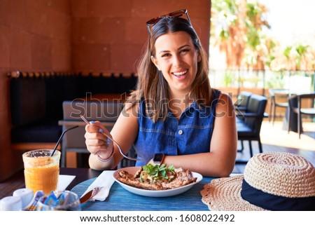 Young beautiful woman sitting at restaurant enjoying summer vacation eating delicious food #1608022492