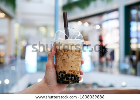 Iced Boba/Bubble Milk tea. A plastic cup of milk tea with boba/bubble tapioca pearls and brown sugar syrup, topped with milk foam. #1608039886