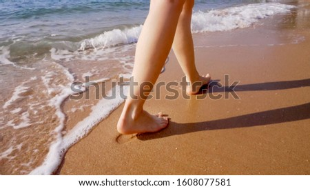 A woman walks along the golden sand of a beach. Female legs walk by the sea. Bare feet of a woman walking along a sandy shore with waves. Summer vacation or vacation. #1608077581