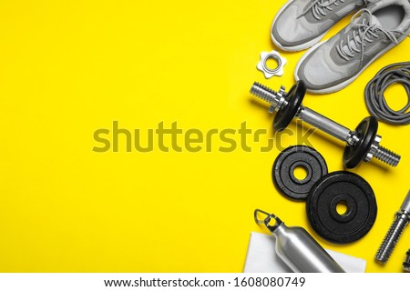 Gym equipment on yellow background, flat lay. Space for text Royalty-Free Stock Photo #1608080749