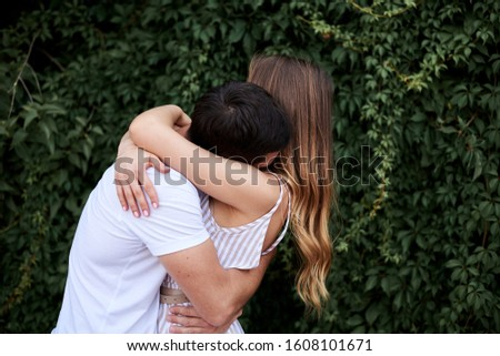Young couple in love hugging near green bushes trees wall. Pretty blond woman, wearing stripy short overall and brunette man in white t-shirt and blue shorts on romantic date. Romantic relationship #1608101671