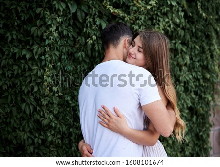 Young couple in love hugging near green bushes trees wall. Pretty blond woman, wearing stripy short overall and brunette man in white t-shirt and blue shorts on romantic date. Romantic relationship #1608101674