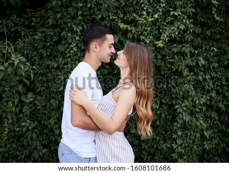 Young couple in love hugging near green bushes trees wall. Pretty blond woman, wearing stripy short overall and brunette man in white t-shirt and blue shorts on romantic date. Romantic relationship #1608101686