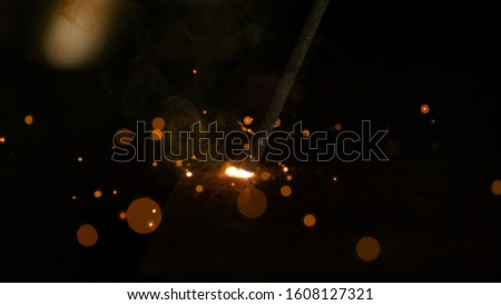 MACRO, DOF: Round weld glows in the dark workshop as an unrecognizable metalworker welds a piece of metal. Glowing orange parks fly off a craftsman's welding torch as he welds an iron workpiece. #1608127321