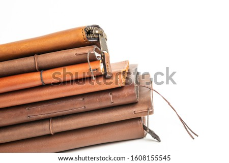 A stack of leather-bound journals, notebooks, cases and wallets set on a plain white background. #1608155545