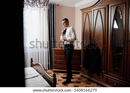 Morning groom in the room. Wedding photography. Groom getting ready in the room for wedding day. Details. Fees of the groom. The groom straightens his tie #1608166279