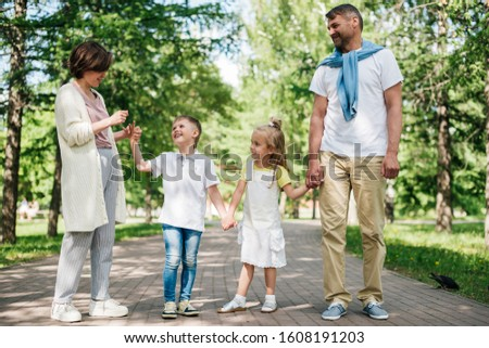 Parents with two kids walk in the park and speak to them. #1608191203