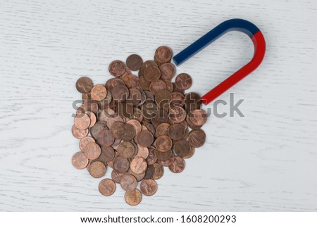 Magnet attracting coins on white wooden table, flat lay #1608200293