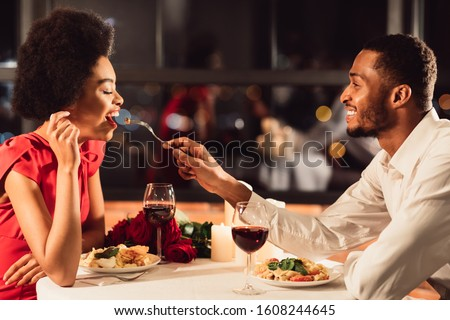 Romantic Date Concept. African American Man Feeding Girlfriend During Dinner Celebrating Anniversary In Restaurant #1608244645