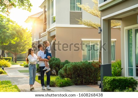 Beautiful family portrait smiling outside their new house with sunset, this photo canuse for family, fathe, mother and home concept #1608268438
