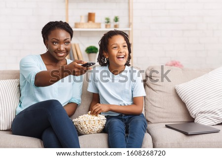 Mother With Daughter. Happy black family watching tv movie, cartoons or football with popcorn. Copy space