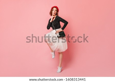 Happy french young woman dancing with smile. Full length view of fashionable girl in red beret standing on one leg. #1608313441