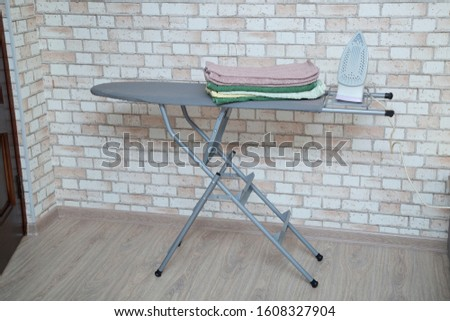 Ironing Board with iron and ironed towels. #1608327904